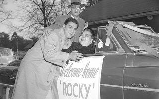 Ο διάσημος πυγμάχος Ρόκι Μαρτσιάνο, ο μοναδικός πρωταθλητής βαρέων βαρών στην ιστορία της πυγμαχίας που τελείωσε την καριέρα του αήττητος, δέχεται το καλωσόρισμα των γονιών του στο δημοτικό αεροδρόμιο του Μπρόκτον της Μασαχουσέτης, στην πρώτη του επίσκεψη στο σπίτι του, μετά τη νίκη του επί του πρώην παγκόσμιου πρωταθλητή Τζο Λιούις. (AP Photo)