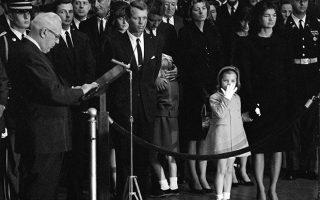 Η Ζακλίν Μπουβιέ κρατά το χέρι της κόρης της, Κάρολαϊν, καθώς ο ανώτατος δικαστικός Ερλ Ουόρεν διαβάζει τον επικήδειο λόγο του για τον δολοφονημένο πρόεδρο Τζον Φ. Κένεντι, στην Ροτόντα του Καπιτωλίου, στην Ουάσιγκτον, το 1963. Στη φωτογραφία διακρίνονται ο νέος πρόεδρος των ΗΠΑ, Λίντον Τζόνσον και ο αδερφός του δολοφονημένου Αμερικανού προέδρου, Ρόμπερτ Κένεντι. (AP Photo)