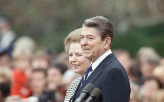O Αμερικανός πρόεδρος Ρόναλντ Ρήγκαν και η Βρετανίδα πρωθυπουργός Μάργκαρετ Θάτσερ, οι κύριοι εκπρόσωποι της πολιτικής του νεοφιλελευθερισμού, στέκονται δίπλα ο ένας στον άλλο, κατά τη διάρκεια τελετής για την υποδοχή της τελευταίας στις Ηνωμένες Πολιτείες, το 1988. (AP Photo/Doug Mills)
