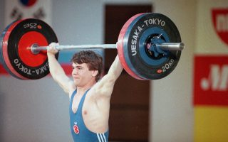 Turkish weightlifter Naim Suleymanoglu strains during the International Sports Fair, May 4, 1989, in Tokyo. (AP Photo/Shizuo Kambayashi)