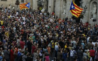 People take part during a protest called by pro-independence groups outside of the Palau Generalitat in Barcelona, Spain, Wednesday, Oct. 25, 2017. Catalonia's vice president says Spanish authorities are giving separatists in the prosperous northeastern region