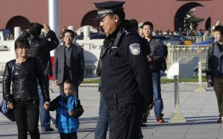epa03928705 A Chinese police officer with a fire extinguisher within his reach keeps watch at Tiananmen Square fronting the Forbidden City at Tiananmen Square in Beijing, China, 29 October 2013. According to media reports, Chinese police have named two men from a restive far western region as suspects after a car crashed through barriers, ploughed into a crowd of tourists and police, and burst into flames in front of the famous Tiananmen gate in central Beijing on 28 October.  EPA/ROLEX DELA PENA