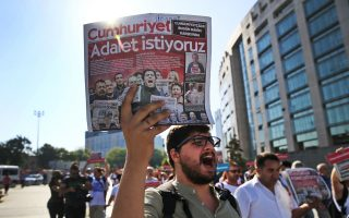 Activists, one holding today's copy of the Cumhuriyet newspaper, march to the court in Istanbul, Monday, July 24, 2017, protesting against a trial of journalists and staff from the newspaper, accused of aiding terror organizations. The newspaper headline reads in Turkish:
