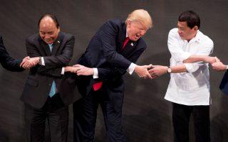 Ο Ντόναλντ Τραμπ σε «ασιατικού τύπου» χειραψία με τον Βιετναμέζο πρωθυπουργό Νγκουγιέν Σουάν Φουκ (αριστερά) και τον πρόεδρο των Φιλιππίνων Ροντρίγκο Ντουτέρτε (δεξιά) στη σύνοδο κορυφής της Οικονομικής Συνεργασίας Ασίας - Ειρηνικού.