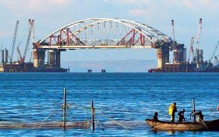 Ψαράδες μαζεύουν τα δίχτυα τους με φόντο τις αψίδες της υπό κατασκευήν γέφυρας που θα συνδέει τη ρωσική ενδοχώρα με τη χερσόνησο της Κριμαίας. To φιλόδοξο έργο, συνολικού κόστους 7 δισ. δολαρίων, έχει περισσότερο συμβολική παρά πρακτική αξία. Εντάσσεται σε μια σειρά από μεγάλα έργα υποδομής, που τόσο αγαπά ο Ρώσος πρόεδρος Βλαντιμίρ Πούτιν.