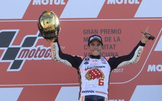 Moto GP World Champion winner Marc Marquez of Spain celebrates on the podium after finishing third at the Valencia Motorcycle Grand Prix, the last race of the season, at the Ricardo Tormo circuit in Cheste near Valencia, Spain, Sunday Nov. 12, 2017. Marquez won his fourth MotoGP world title on Sunday after challenger Andrea Dovizioso crashed during the season-concluding Valencia Grand Prix. (AP Photo/Alberto Saiz)