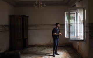 Ο Θωμάς Μπόνο μέσα στο σαλόνι του σπιτιού του. Η στάθμη του νερού έφτασε μέχρι το μέτωπό του. (Φωτογραφία: Enri Canaj)