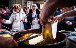 Ναπολιτάνοι σεφ πίτσας γιορτάζουν την ένταξη του παραδοσιακού εδέσματος στον κατάλογο με την άυλη κληρονομιά της UNESCO, προσφέρο-ντας κομμάτια πίτσας στους διερχομένους.