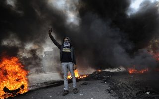 epa06377346 A Palestinian masked militant protesters attends a protest against the US President's decision to recognize Jerusalem as the capital of Israel, during clashes along the border between Israel and east Gaza, Gaza Strip, Gaza Strip, 08 December 2017. US President Trump on 06 December announced he is recognising Jerusalem as the Israel capital and will relocate the US embassy from Tel Aviv to Jerusalem.  EPA/MOHAMMED SABER