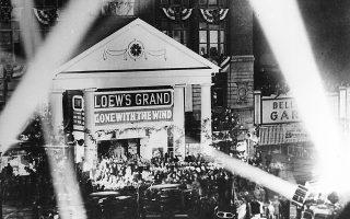 Η επική ιστορική ρομαντική ταινία του Βίκτορ Φλέμινγκ, «Όσα Παίρνει ο Άνεμος», κάνει πρεμιέρα στο Loew's Grand Theatre της Ατλάντα, κορυφώνοντας τρεις ημέρες εκδηλώσεων για την προώθηση της ταινίας στην πόλη, στις οποίες παρευρέθησαν οι αστέρες της ταινίας, το 1939. Τουλάχιστον 300.000 άτομα κατέφθασαν στην πρωτεύουσα της Τζόρτζια για το εορταστικό τριήμερο. (AP Photo)