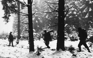 Άνδρες του πεζικού της πρώτης αμερικανικής στρατιάς βαδίζουν με δυσκολία ανάμεσα στα χιονισμένα ψηλά δέντρα του δάσους του Κρίνκελτερ, στο Βέλγιο, καθώς προσεγγίζουν τις γραμμές του εχθρού, το 1944. (AP Photo)