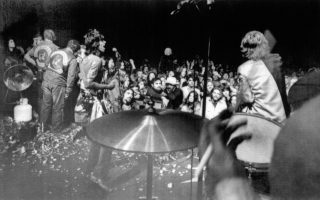 Οι headliners της θρυλικής «Δωρεάν Συναυλίας του Άλταμοντ», Rolling Stones, παίζουν μπροστά σε ένα κοινό περίπου 300.000 ατόμων, στην Καλιφόρνια, το 1969. Αριστερά, διακρίνονται μέλη των διαβόητων μηχανόβιων «Άγγελων του Θανάτου» (Hell's Angels), οι οποίοι είχαν αναλάβει να επιβλέψουν την τάξη και την ασφάλεια στη συναυλία, να προσπαθούν να απομακρύνουν θεατές που προσπαθούν να ανέβουν στη σκηνή. Παρότι αρχικά η συναυλία προοριζόταν να γίνει κάτι σαν ένα «Γούντστοκ της Δύσης», λιγότερο από τέσσερις μήνες μετά το «αυθεντικό» Γούντστοκ, η «Δωρεάν Συναυλία του Άλταμοντ» υπήρξε η αντιστροφή των όσων πρέσβευε το θρυλικό φεστιβάλ της αγάπης, του έρωτα και της ειρήνης. Η συναυλία αμαυρώθηκε από τη βία των Hell's Angels, η οποία προκάλεσε τον θάνατο ενός Αφροαμερικανού, καθώς και άπο άλλους τρεις θανάτους, δύο από αυτοκινητιστικό δυστύχημα και έναν από πνιγμό σε αρδευτικό κανάλι υπό την επιρροή LSD. (AP Photo)