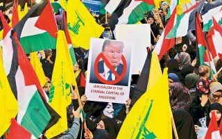 Μια Λιβανέζα που κρατάει πορτρέτο του Ντόναλντ Τραμπ και άλλοι διαδηλωτές με σημαίες της Παλαιστίνης και της Χεζμπολάχ στη Βηρυτό.