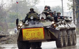A Russian army armored personnel carrier (APC) patrols a street of Grozny, 28 October 2005. Two soldiers and a policeman were badly wounded in a roadside blast targeting their convoy in the centre of the Chechen capital Grozny, police and doctors said.  AFP PHOTO / KHASAN KAZIYEV