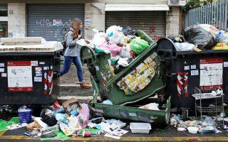 Μια γυναίκα περπατά δίπλα σε συσσωρευμένα σκουπίδια στην ιταλική πρωτεύουσα.