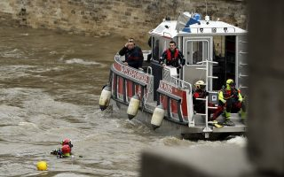 epa06418626 French Police and firefighters during a rescue operation on the Seine river after a female Police officer have been swept away during a training exercises in Paris, France, 05 January 2018. The missing officer was taking part in diving training exercises, according to reports.  EPA/YOAN VALAT