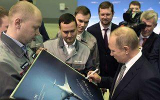 Ο πρόεδρος Πούτιν υπογράφει αυτόγραφα πάνω στην εικόνα του νέου υπερηχητικού βομβαρδιστικού Tu-160M.