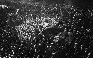 Σκεπασμένο με ροδοπέταλα και περιτριγυρισμένο από πλήθος κόσμου που τον λατρεύει σαν Άγιο, το άψυχο σώμα του Ινδού ειρηνιστή ηγέτη Μαχάτμα Γκάντι βαίνει προς το σημείο που θα αποτεφρωθεί, μία μέρα μετά τη δολοφονία του, στο Νέο Δέλχι, το 1948. (AP Photo/Max Desfor)