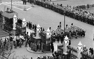 Το σκεπασμένο με τη βρετανική σημαία φέρετρο που αναπαύεται ο πρώην Βρετανός πρωθυπουργός και ένας εκ των νικητών του Β´Παγκοσμίου Πολέμου, Ουίνστον Τσόρτσιλ,  περνά τις πύλες της Αίθουσας του Ουέστμινστερ, με κατεύθυνση τον καθεδρικό ναό του Αγίου Παύλου, όπου θα διεξαχθεί η κηδεία του ιστορικού πολιτικού, το 1965. (AP Photo)