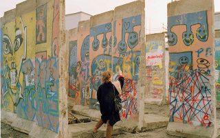ψMία επισκέπτρια χαζεύει τα γκράφιτι που σκεπάζουν αυτά τα αποκομμένα κομμάτια του Τείχους του Βερολίνου, στο Ανατολικό Βερολίνο, το 1990. Τα κομμάτια έχουν τοποθετηθεί με τρόπο, ώστε να μπορεί να τα κοιτάξει κάποιος λεπτομερώς, καθώς προορίζονται για πώληση σε πιθανούς ενδιαφερόμενους για την ιστορική και ενδεχομένως καλλιτεχνική αξία τους. (AP Photo/Roland Weihrauch)