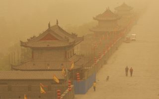 Visitors walk along the city wall during a sand storm in Xi'an, in northwest China's Shaanxi province, April 11, 2006. A cold current is forecast to hit China in the next two days and will cause a drop in temperature in the north and bring strong rains to the south, according to the China Meteorological Administration (CMA) on Sunday. CHINA OUT REUTERS/China Daily