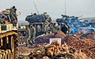 Τούρκοι στρατιώτες επιθεωρούν άρματα μάχης προτού περάσουν τα σύνορα με τη Συρία, κατευθυνόμενοι προς την κουρδική πόλη Αφρίν, στο βόρειο τμήμα της χώρας.