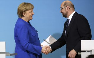German Chancellor Angela Merkel, left, shakes hand with Social Democratic Party Chairman Martin Schulz during a joint statement after the exploratory talks between Merkel's Christian Democratic block and the Social Democrats on forming a new German government in Berlin, Germany, Friday, Jan. 12, 2018. (AP Photo/Markus Schreiber)