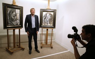 Russian businessperson and President of French football club AS Monaco Dmitry Rybolovlev poses in Paris on September 24, 2015 in front of two allegedly stolen paintings by Pablo Picasso, including 'Woman with a Fan' (L), which he purchased from a Swiss art dealer. A Paris court on September 16 charged a Swiss art dealer with handling stolen goods in a case relating to the alleged theft of Picasso works, which were bought by Russian billionaire Dmitri Rybolovlev. AFP PHOTO / PATRICK KOVARIK  --RESTRICTED TO EDITORIAL USE, MANDATORY MENTION OF THE ARTIST UPON PUBLICATION, TO ILLUSTRATE THE EVENT AS SPECIFIED IN THE CAPTION--