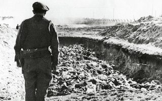 1945, στρατόπεδο συγκέντρωσης Μπέργκεν-Μπέλσεν. Βρετανός αξιωματικός μπροστά σε μια τάφρο γεμάτη πτώματα.