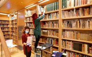 Με μάσκες στο πρόσωπο και γάντια στα χέρια, δύο εξειδικευμένες υπάλληλοι της Εθνικής Βιβλιοθήκης της Ελλάδος τοποθετούν τα βιβλία στα ράφια ενός από τα αναγνωστήρια του νέου κτιρίου στο Κέντρο Πολιτισμού Ιδρυμα Σταύρος Νιάρχος. Το έργο της μεταφοράς των βιβλίων συνεχίζεται και χρηματοδοτείται από το ελληνικό κράτος με 500.000 ευρώ, ενώ υπολογίζεται να ολοκληρωθεί εντός τριών μηνών. Αργότερα θα ακολουθήσουν η αποκατάσταση του Βαλλιανείου και η αξιοποίησή του από την ΕΒΕ.