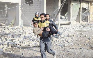 Μέλος της συριακής οργάνωσης πολιτικής προστασίας «Λευκά Κράνη» απομακρύνει αγοράκι που τραυματίστηκε από τους συνεχιζόμενους αεροπορικούς βομβαρδισμούς στην Ανατολική Γούτα, στα περίχωρα της Δαμασκού.