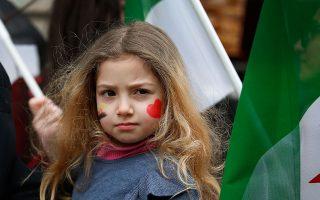 Ανάμεσα σε συριακές σημαίες,  το κοριτσάκι της φωτογραφίας συνοδεύει τη μητέρα του σε διαδήλωση έξω από το ρωσικό προξενείο της Κωνσταντινούπολης.