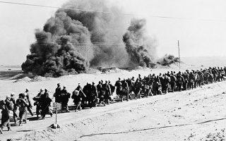 Περίπου 7.500 αιχμάλωτοι πολέμου των Βρετανών, κυρίως στρατιώτες του «Αφρικανικού Σώματος» (Afrika Korps) της Βέρμαχτ, εγκαταλείπουν τη Μπάρντια της Λιβύης, μετά την κατάληψη της από τα συμμαχικά στρατεύματα πριν από περίπου ένα μήνα, το 1942. Oι φλεγόμενες προμήθειες τους έχουν δημιουργήσει ένα πελώριο σύννεφο καπνού στο βάθος. (AP Photo)