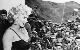 Χρόνια πριν από τις επισκέψεις Αμερικανών ηθοποιών και καλλιτεχνών στα πολεμικά μέτωπα του Βιετνάμ τη δεκαετία του '60, η Μέριλιν Μονρόε διασκεδάζει τους πεζοναύτες μιας αμερικανικής στρατιωτικής μονάδας στην κορεατική χερσόνησο, στην πρώτη στάση της τετραήμερης περιοδείας της στην Κορέα, κατά τη διάρκεια του πολέμου της Κορέας, το 1954. (AP Photo/Gene Smith)