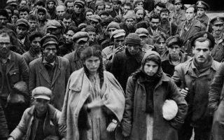 Αντάρτες και αντάρτισσες του Δημοκρατικού Στρατού έχουν μόλις συλληφθεί από άντρες του Εθνικού Στρατού και μεταφέρονται στη Θεσσαλονίκη, μετά τον κανονιοβολισμό εναντίον της συμπρωτεύουσας από τον ΔΣΕ, πριν από δύο ημέρες, το 1948. (AP Photo)