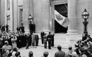 Η σημερινή σημαία του Καναδά, ευρύτερα γνωστή ως Φύλλο Σφενδάμνου ή Μονόφυλλη, υψώνεται για πρώτη φορά στην κεντρική είσοδο του κτιρίου της καναδικής διπλωματικής αποστολής στη Βρετανία, στην πλατεία Τραφάλγκαρ, στο Λονδίνο, το 1965. (AP Photo)