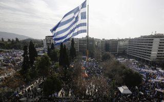 Μια τεράστια Ελληνική σημαία ανεμίζει από γερανό, στην πλατεία Συντάγματος, ενώ διαδηλωτές  παίρνουν μέρος στο συλλαλητήριο ενάντια στην χρήση του ονόματος