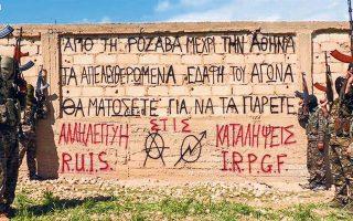Σύνθημα γραμμένο στα ελληνικά από Ελληνες αναρχικούς, που φωτογραφίζονται με Κούρδους μαχητές στη Ροζάβα του δυτικού Κουρδιστάν.