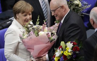 German Chancellor Angela Merkel receives flowers by Christian Democratic parties faction leader Volker Kauder after she has been elected for a fourth term as chancellor in Berlin, Germany, Wednesday, March 14, 2018. (AP Photo/Michael Sohn)