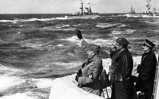 O Ιταλός δικτάτορας Μπενίτο Μουσολίνι χαιρετά φασιστικά το πλήρωμα ενός πολεμικού πλοίου του ιταλικού στόλου, κατά τη διάρκεια άσκησης στα ανοιχτά του λιμανιού της Τρίπολης, στη Λιβύη, η οποία βρισκόταν επί ιταλική κυριαρχία από το 1911 και καθ' όλη τη διάρκεια του φασιστικού καθεστώτος, το 1937. (AP Photo)