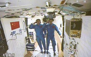 In this image taken off the screen at the Beijing Aerospace Control Center on Wednesday, Oct. 19, 2016 and released by Xinhua News Agency, two Chinese astronauts Jing Haipeng, left and Chen Dong salute in the space lab Tiangong 2. China says a pair of astronauts aboard have entered the country's orbiting space station for a month-long stay. Chinese character on bottom left reads