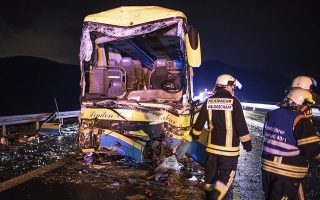 Firefighters stand next to a bus that crashed on highway A3 near Aschaffenburg, Germany, Saturday, March 31, 2018. Police in Germany say a bus driver has been killed and more than a dozen other people were injured when the bus drove into a truck on the Bavarian highway. German news agency dpa reports that police said about 50 people were on the Belgian bus at the time of the accident on the A3 highway near Aschaffenburg. (Frank Rumpenhorst/dpa via AP)