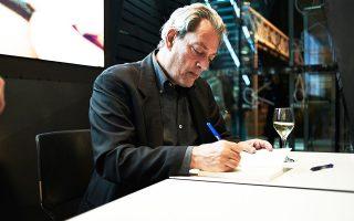 Ο Πολ Οστερ στη Στέγη του Ιδρύματος Ωνάση, τον Νοέμβριο του 2014, υπογράφει βιβλία του για τους Ελληνες αναγνώστες του.