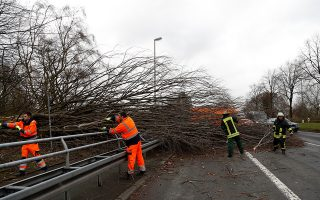epa06450015 Emergency workers remove a fallen tree from a roadway near Dortmund, Germany, 18 January 2018. The storm depression 'Friedrike' is forecast to cause hurricane and heavy rain or snowfall in Germany.  EPA/FRIEDEMANN VOGEL