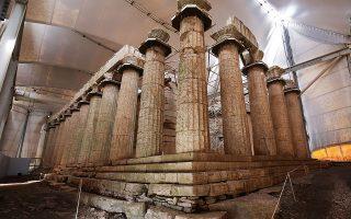 Tα μεταλλικά στεφάνια στην κορυφή των κιόνων και οι οριζόντιες σκαλωσιές είναι το αντισεισμικό ικρίωμα που «δένει» τους κίονες μεταξύ τους.  Εμφανή είναι τα σημάδια υγρασίας και οι φθορές στη βάση του ναού.