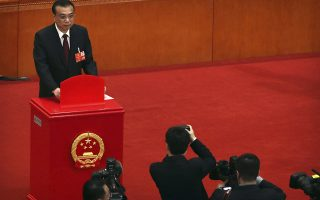 Chinese Premier Li Keqiang casts his ballot during a plenary meeting of China's National People's Congress (NPC) at the Great Hall of the People in Beijing, Sunday, March 18, 2018. China's ceremonial legislature appointed Premier Li Keqiang, the No. 2 leader of the ruling Communist Party, to a second five-year term Sunday and approved the appointment of a director for a new anti-corruption agency with sweeping powers. (AP Photo/Mark Schiefelbein)