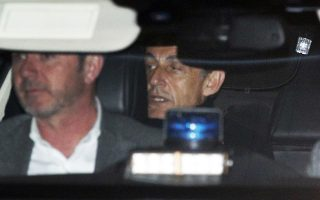 Former French President Nicolas Sarkozy, right, leaves the police station where he was held, in Nanterre, outside Paris, Wednesday March 21, 2018. Former French President Nicolas Sarkozy was questioned by police for a second day Wednesday over allegations he took millions of euros in illegal campaign funding from the late Libyan leader Moammar Gadhafi. (AP Photo/Francois Mori)