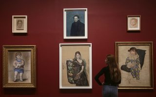 A woman looking at various portraits by Pablo Picasso, during a preview of the exhibition Picasso 1932 - Love, Fame, Tragedy at Tate Modern in London, Tuesday March 6, 2018.  The first ever solo Pablo Picasso exhibition remains at Tate Modern for the summer. (Yui Mok/PA via AP)