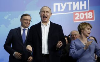 epa06613458 Presidential candidate, Russian President Vladimir Putin (C) reacts as he meets with his supporters at his campaign headquarters in Moscow, Russia, 18 March 2018. Russians are electing the President of Russia in the 18 March elections, with eight candidates contesting for the presidential seat, including the incumbent president Vladimir Putin, who leads with over 72 per cent of the vote and projected to win his fourth term in the Kremlin.  EPA/SERGEI ILNITSKY