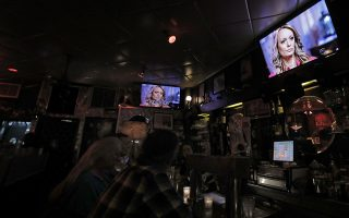 epa06629737 Stephanie Clifford, professionally known as Stormy Daniels, a US adult film actress and director, is seen on screens at the Hi life bar on the upper west side being interviewed on the television show 60 Minutes, in New York, New York, USA, 25 March 2018. Daniels allegedly had a sexual encounter in 2006 with US Presidnent Donald J. Trump.  EPA/PETER FOLEY